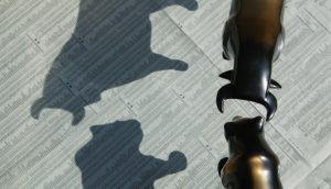 Eine Bär- und eine Bullen-Figur stehen sich bedrucktem Papier gegenüber.