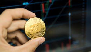 Hand hält eine Dash-Münze, im Hintergrund ein Kurschart