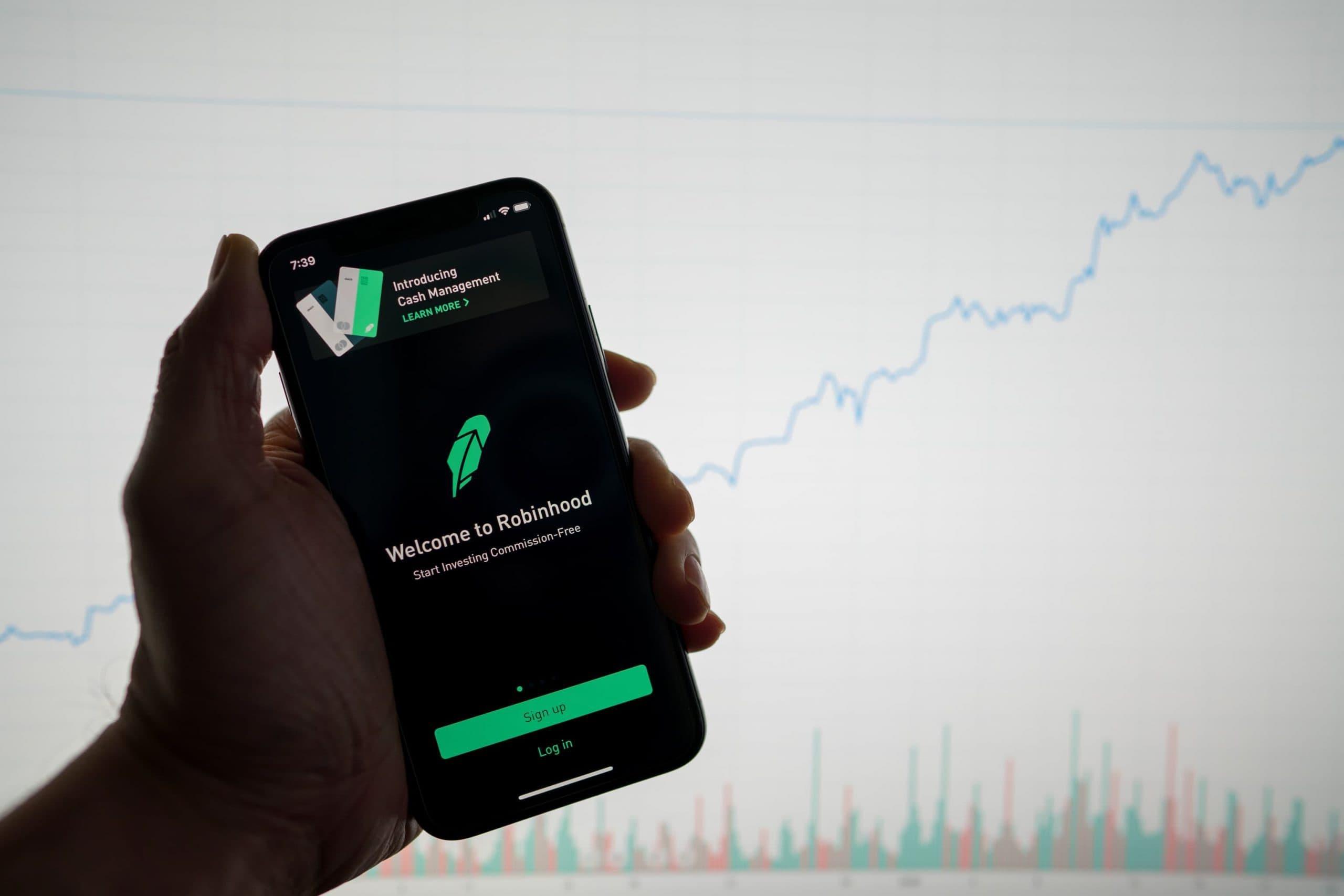 Die Tradig-App Robinhood, dahinter ein Börsen-Chart