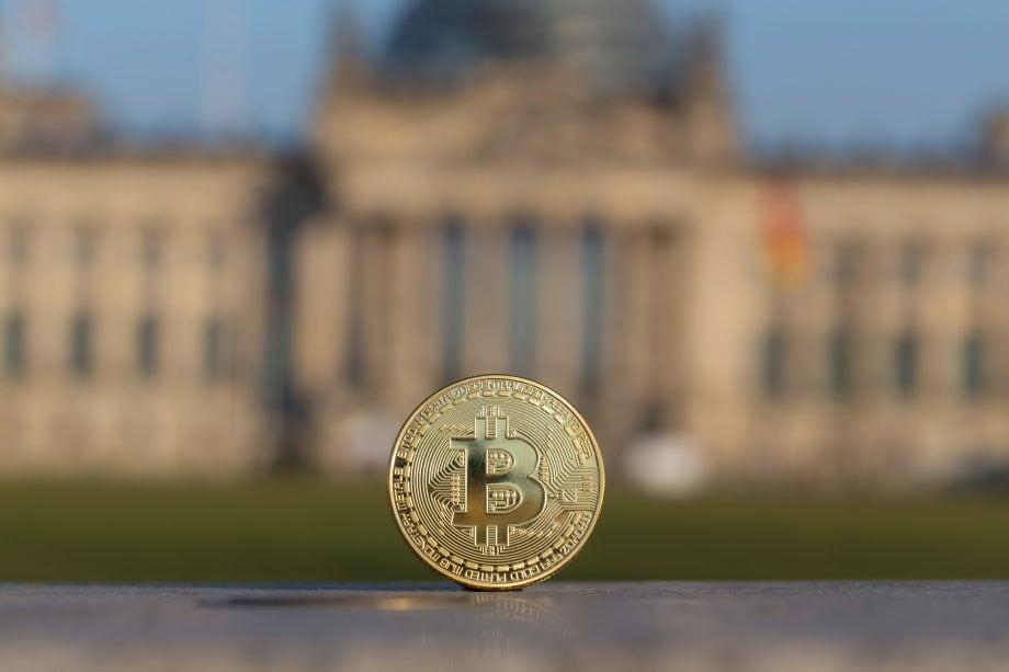 Ein Bitcoin steht senkrecht vor dem deutschen Bundestag.