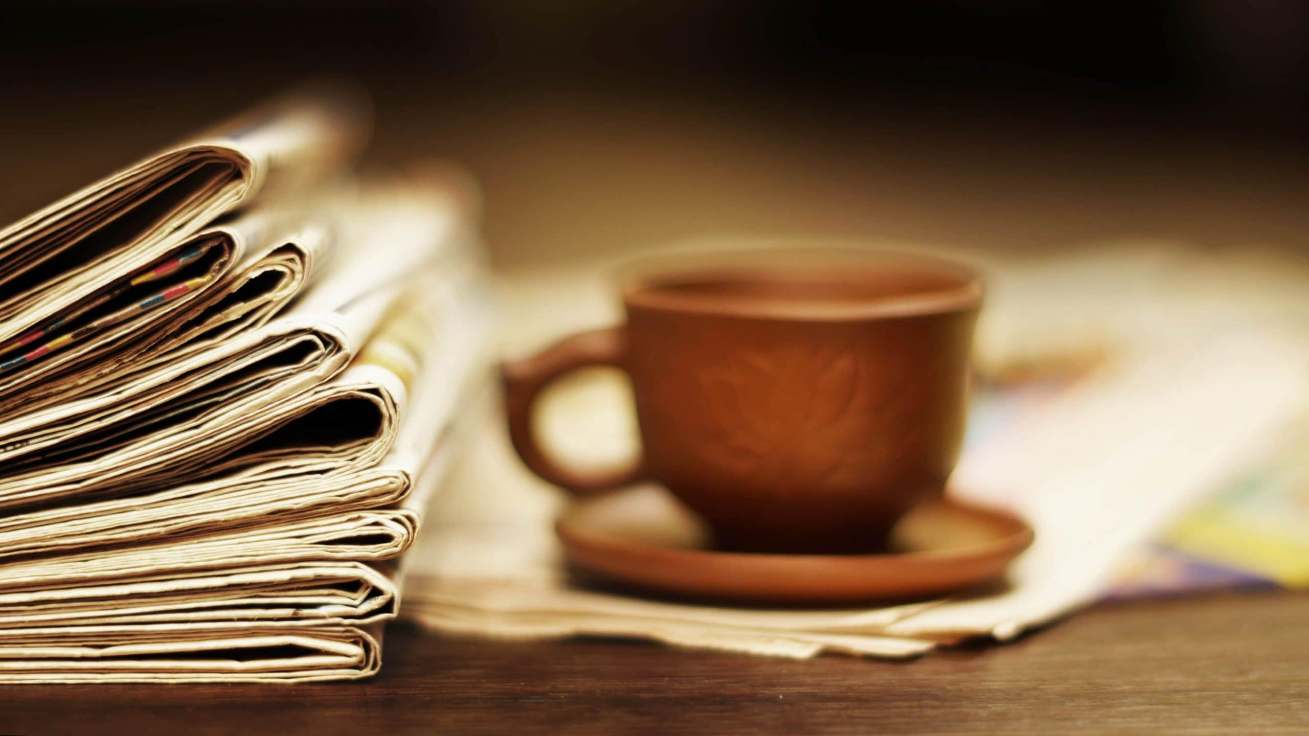 Braune Kaffeetasse steht auf einem Tisch neben einem Stapel Zeitungen.