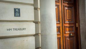 Das Logo der HM Treasury ist auf einer Steinwand zu sehen. Daneben ist eine Steinsäule und eine große, massive Holztür zu sehen.