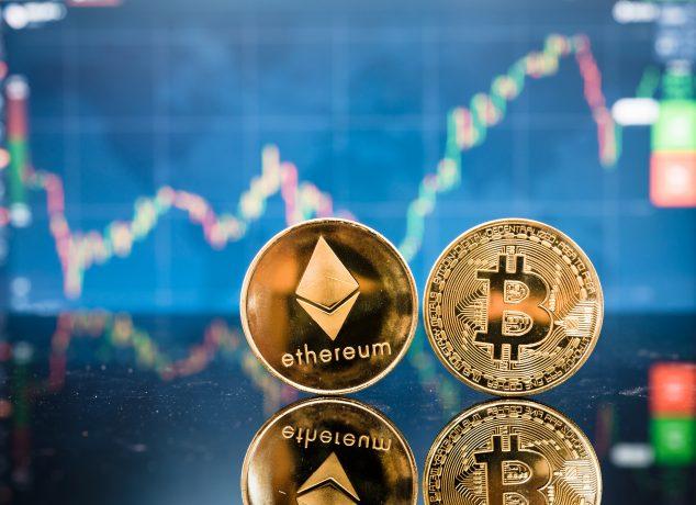 Ethereum- und Bitcoin-Münze vor einem Kursverlauf.