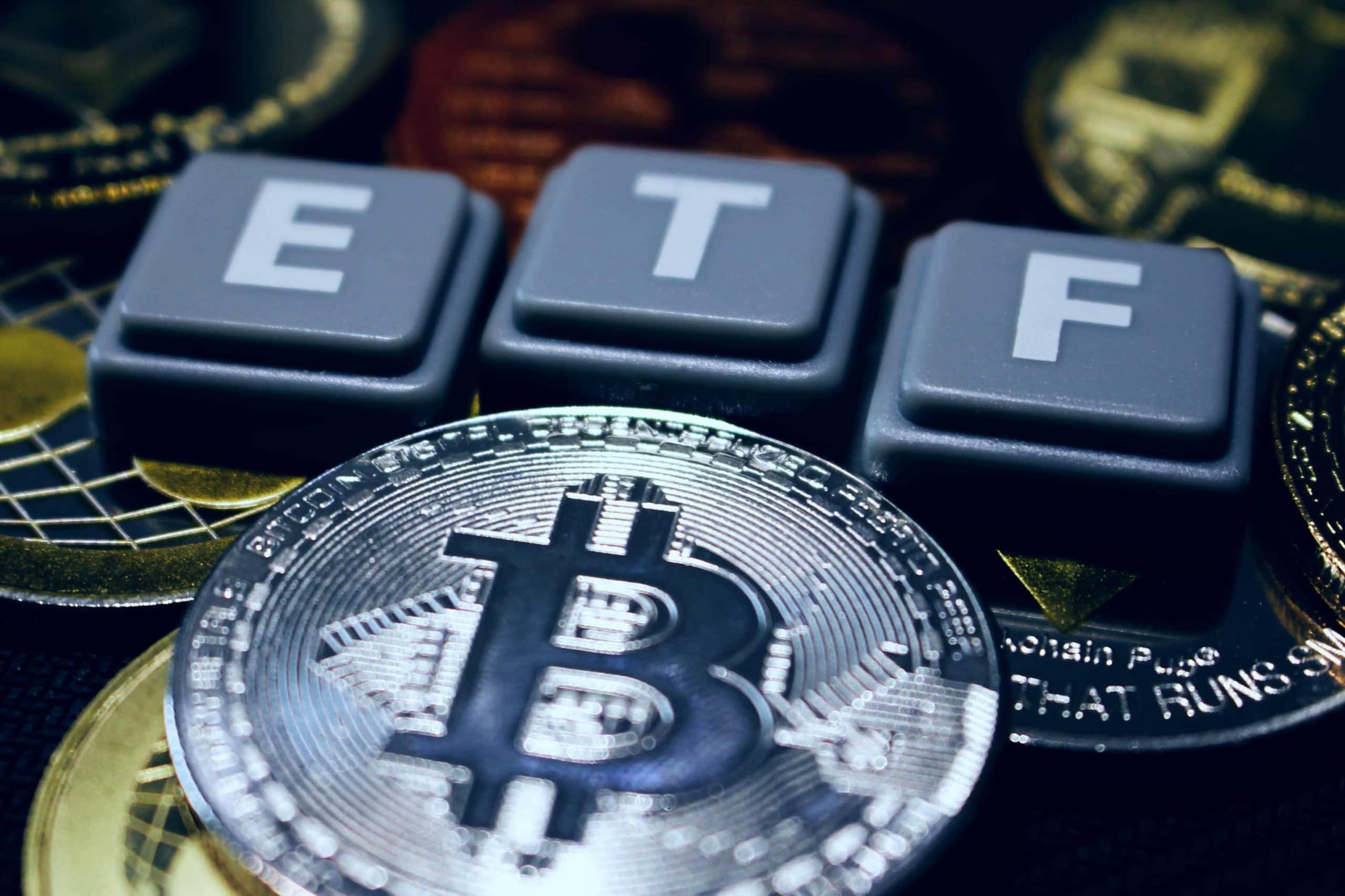 Eine silberne Bitcoin-Münze liegt vor den Tastaturbuchstaben E,T,F.