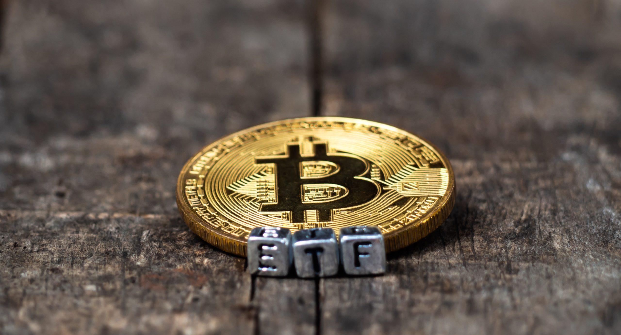 Ein Bitcoin liegt auf einem steinernen Untergrund. Davor sind stehen die Buchstaben E,T,F, als bildliche Verdeutlichung für einen Bitcoin-ETF.