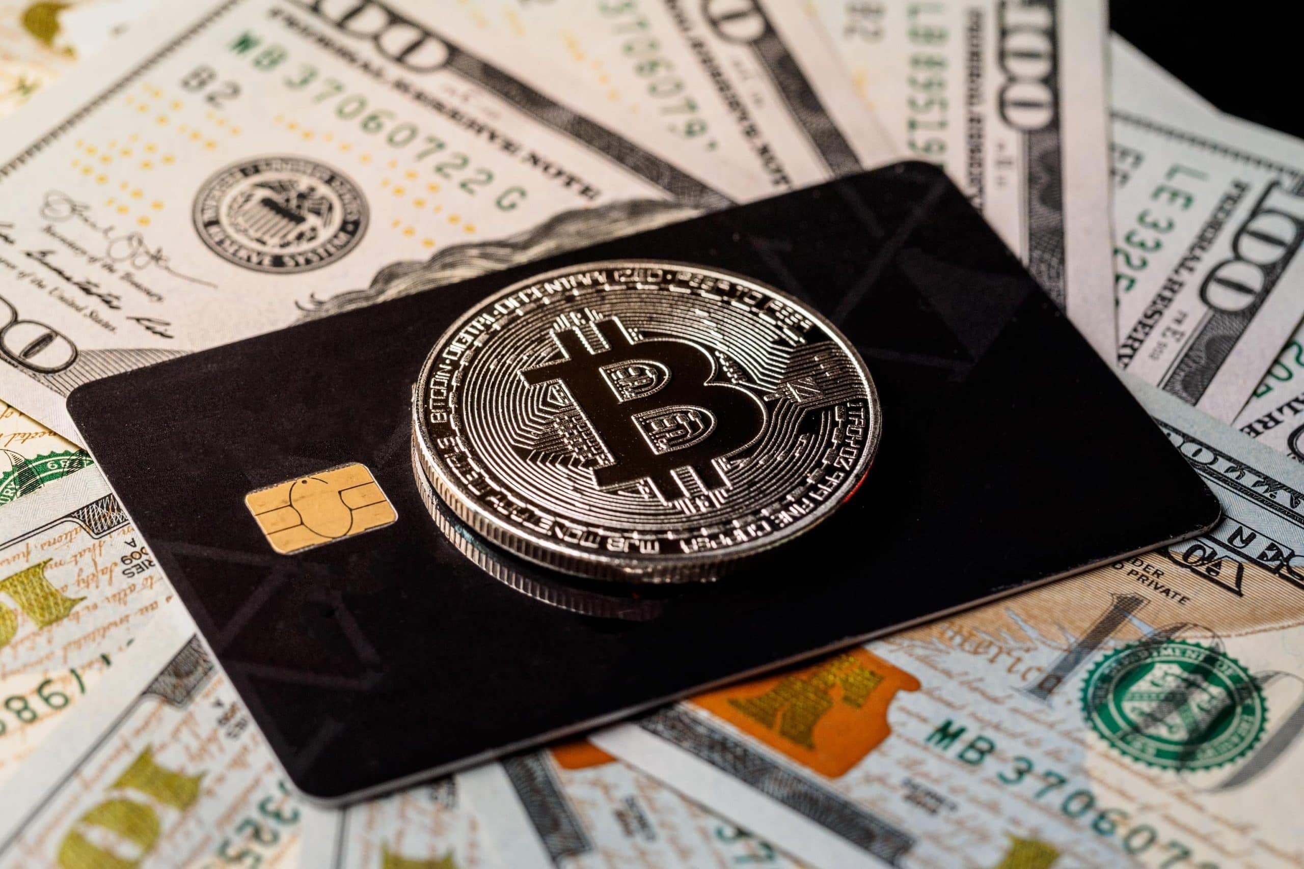 Ein Bitcoin liegt auf einer schwarzen Debitkarte, die auf mehreren US-Dollar-Noten liegt.