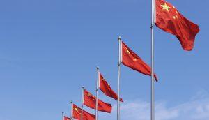 Chinesische Flaggen vor einem blauen Himmel.