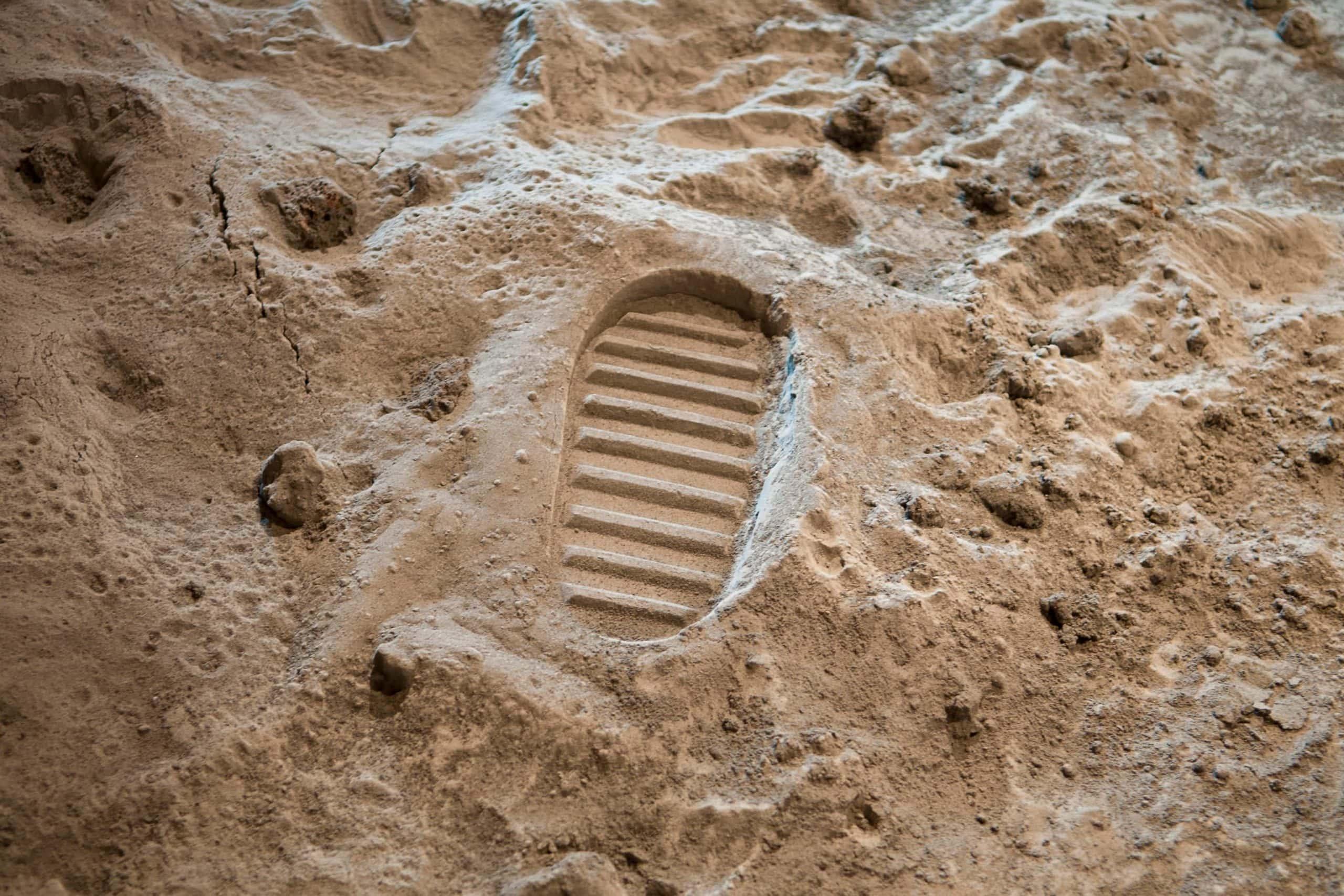 Der Abdruck eines Moonboots im Sand