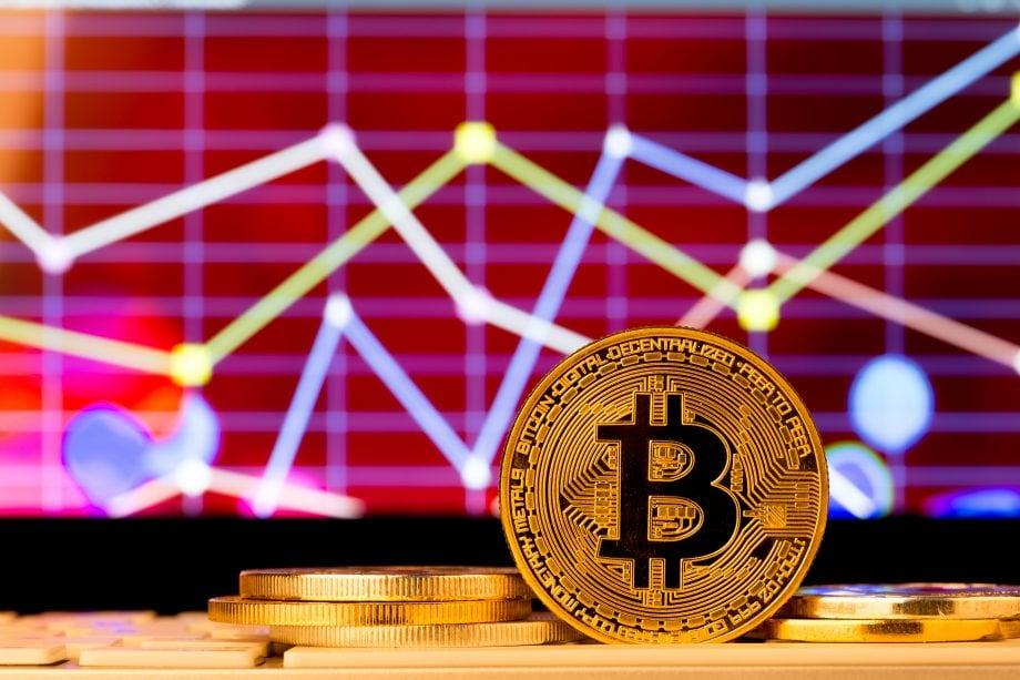 Bitcoin-Münze vor Chart-Hintergrund