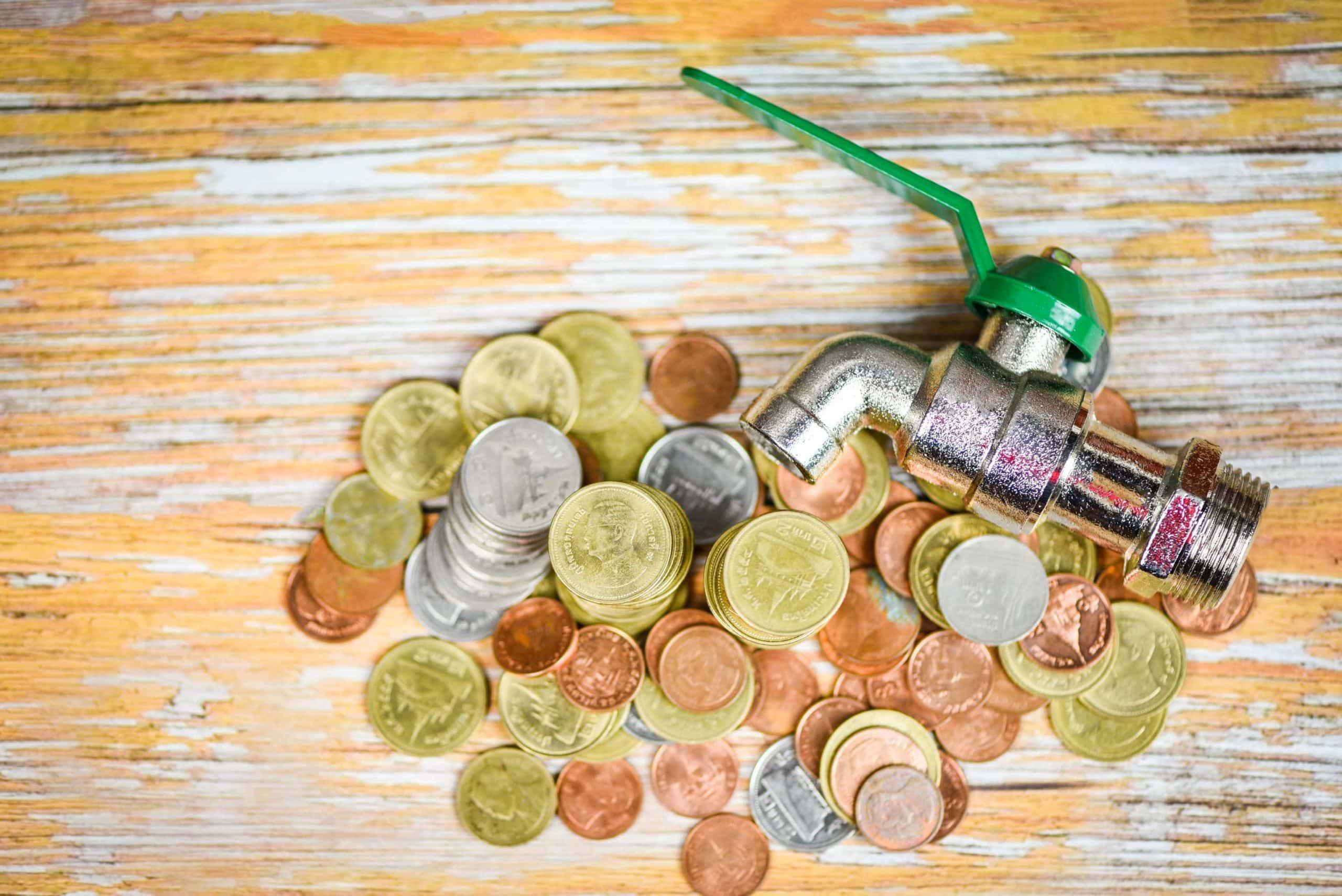 Ein Haufen von Geldmünzen liegen auf einem Holztisch. Daneben liegt ein Wasserhahn. Das verdeutlicht das Bild der Liquidität.
