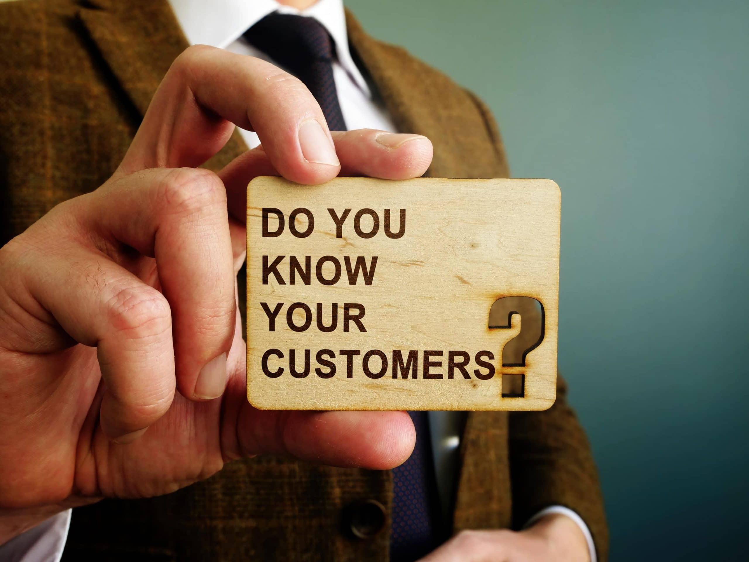 KYC: Ein Mann im Anzug hält ein Schild mit der Aufschrift