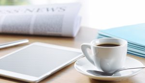 Ein Zeitung, ein Tablet, ein Stapel Blätter und ein Kaffeetasse mit Untersetzter und Löffel stehen auf einem Holztisch.
