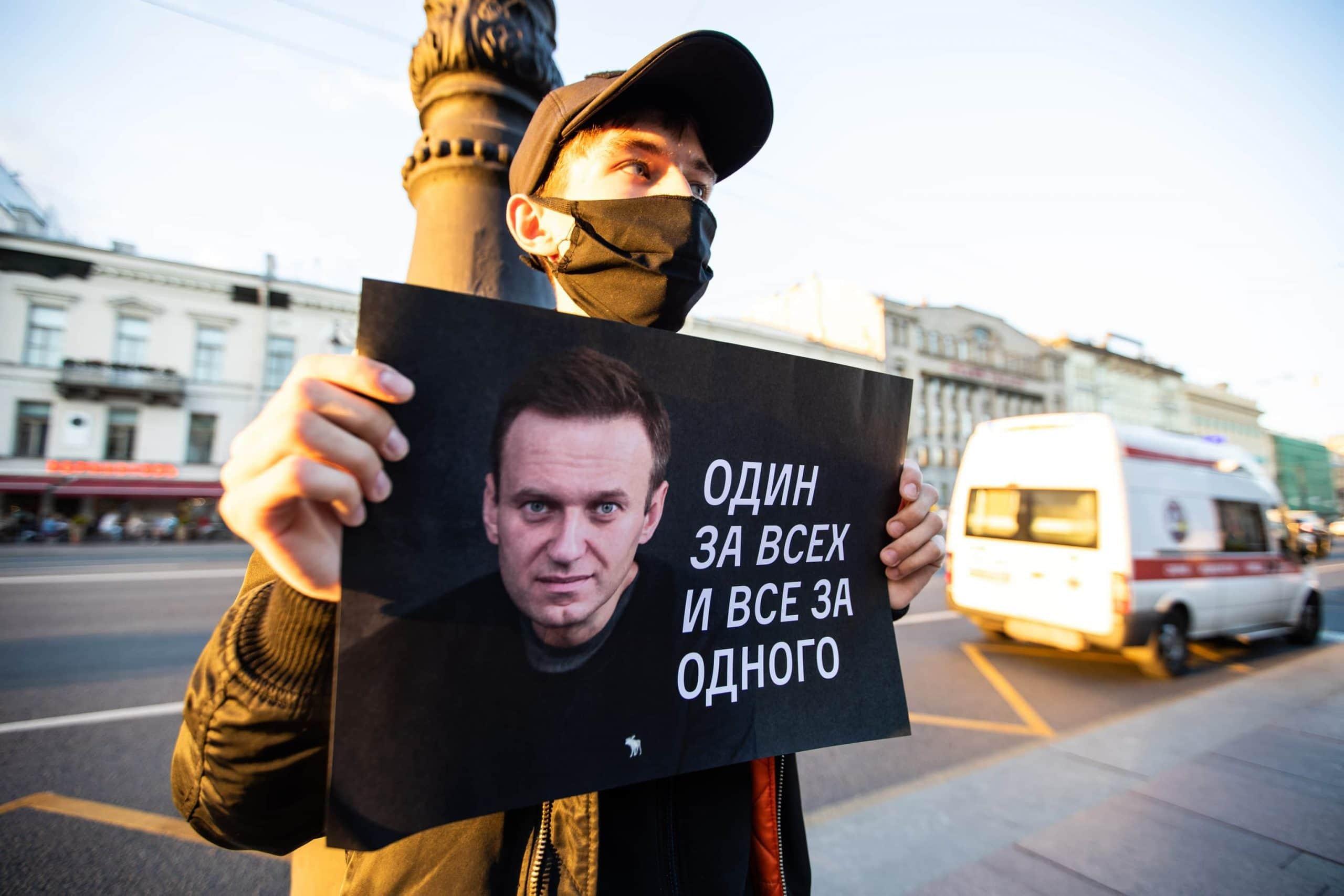 Nawalny-Protestant hält ein Protestschild hoch auf dem Nawalnys Gesicht zu sehen ist. Daneben steht der Spruch: