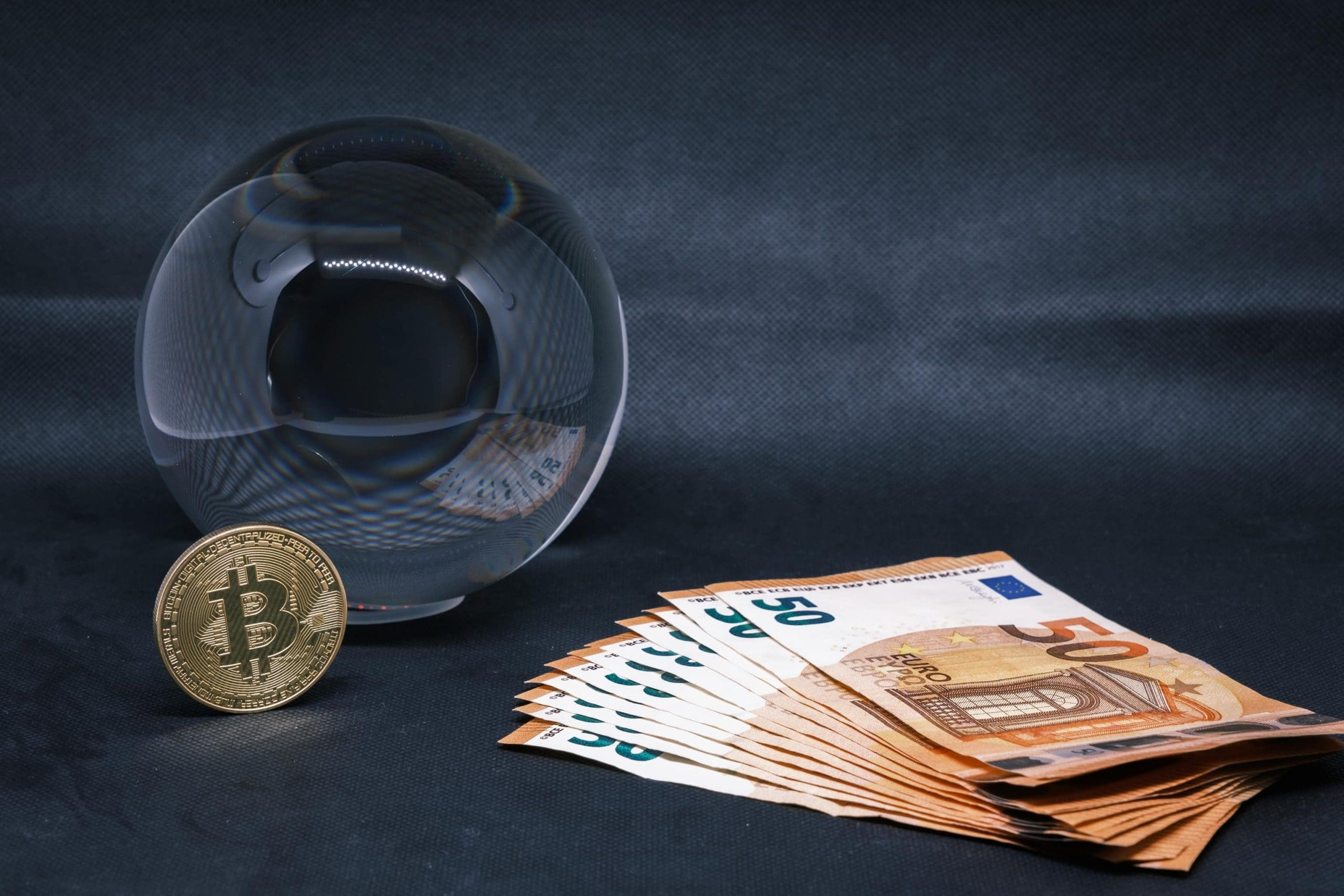 Eine Bitcoin-Münze vor einer Glaskugel, im Vordergrund mehrere 50-Euro-Scheine