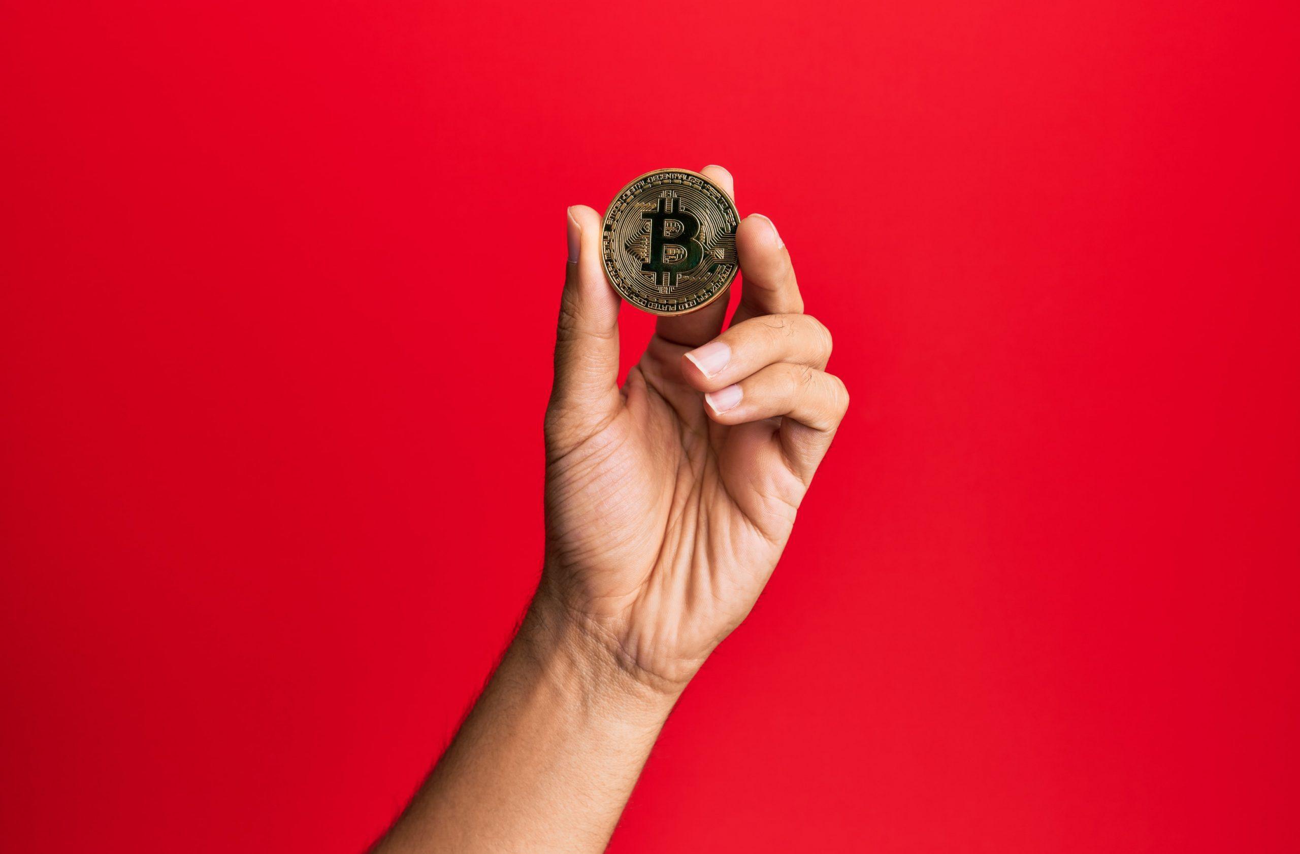 Hand hält Bitcoin-Münze vor rotem Hintergrund