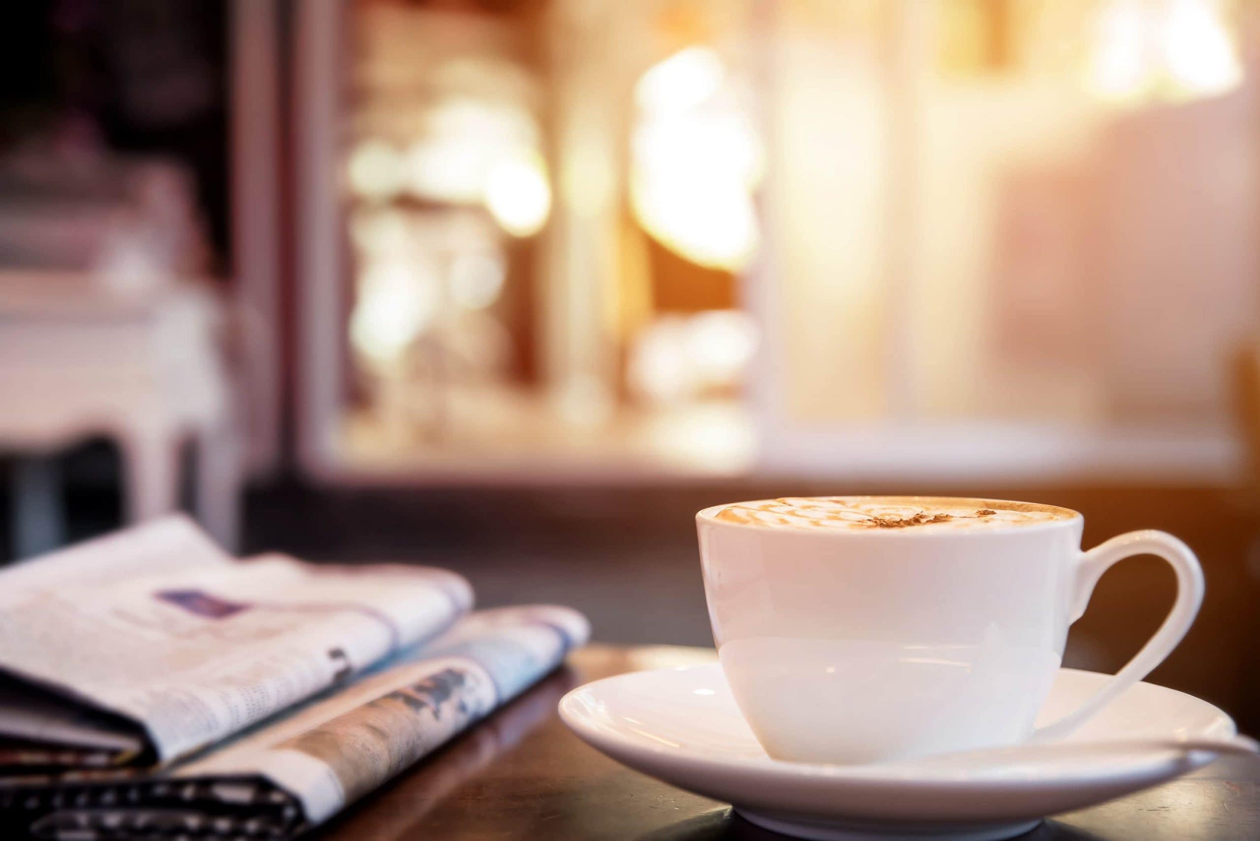 Capucciono-Tasse steht neben zwei Zeitungen auf einem Tisch. Dahinter ist ein geöffnetes Fesnter.
