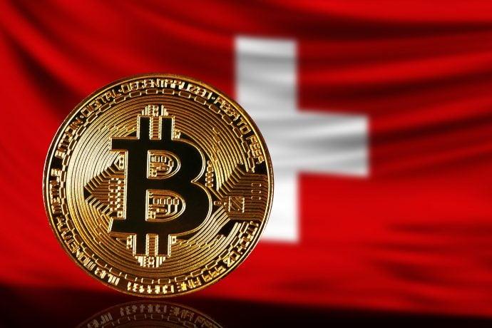 Eine Bitcoin-Münze vor einer Flagge der Schweiz (Bitcoin-ETP).