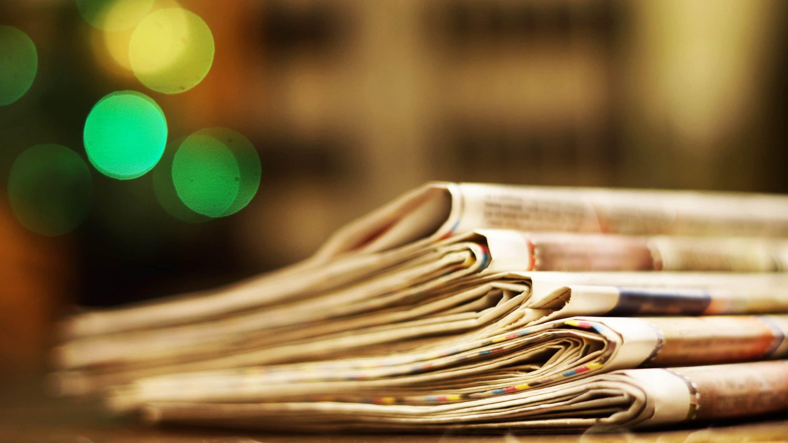 Zeitungen legen auf einem Stapel auf einem Tisch.