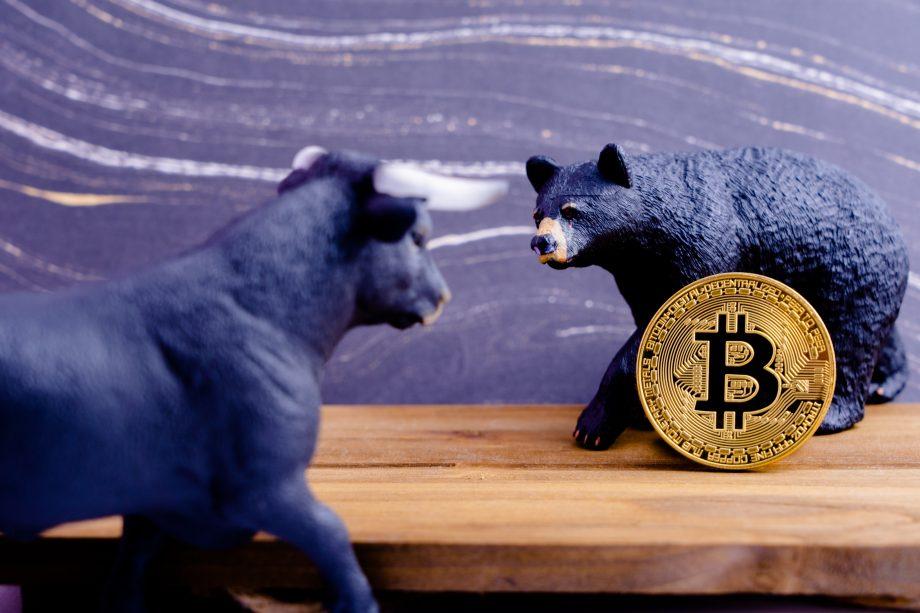 Bitcoin-Münze zwischen Bär- und Bullen-Figur