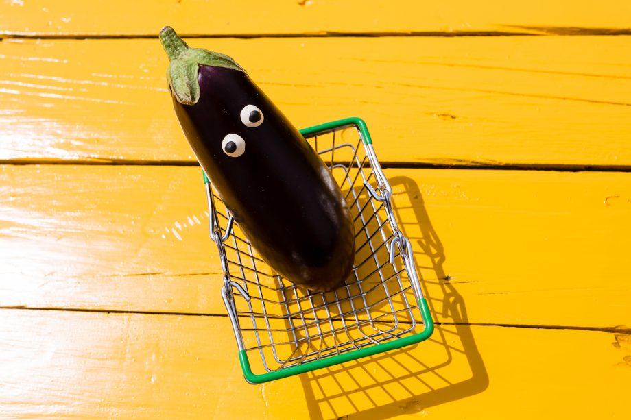 Eine Aubergine mit Augen in einem Einkaufskorb