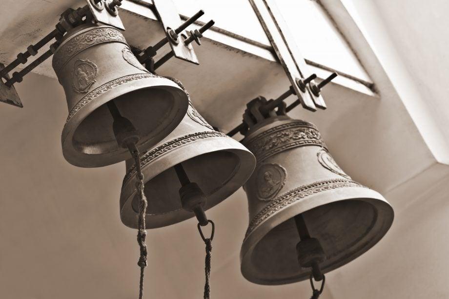 Drei Glocken hängen in einem Kirchenturm.