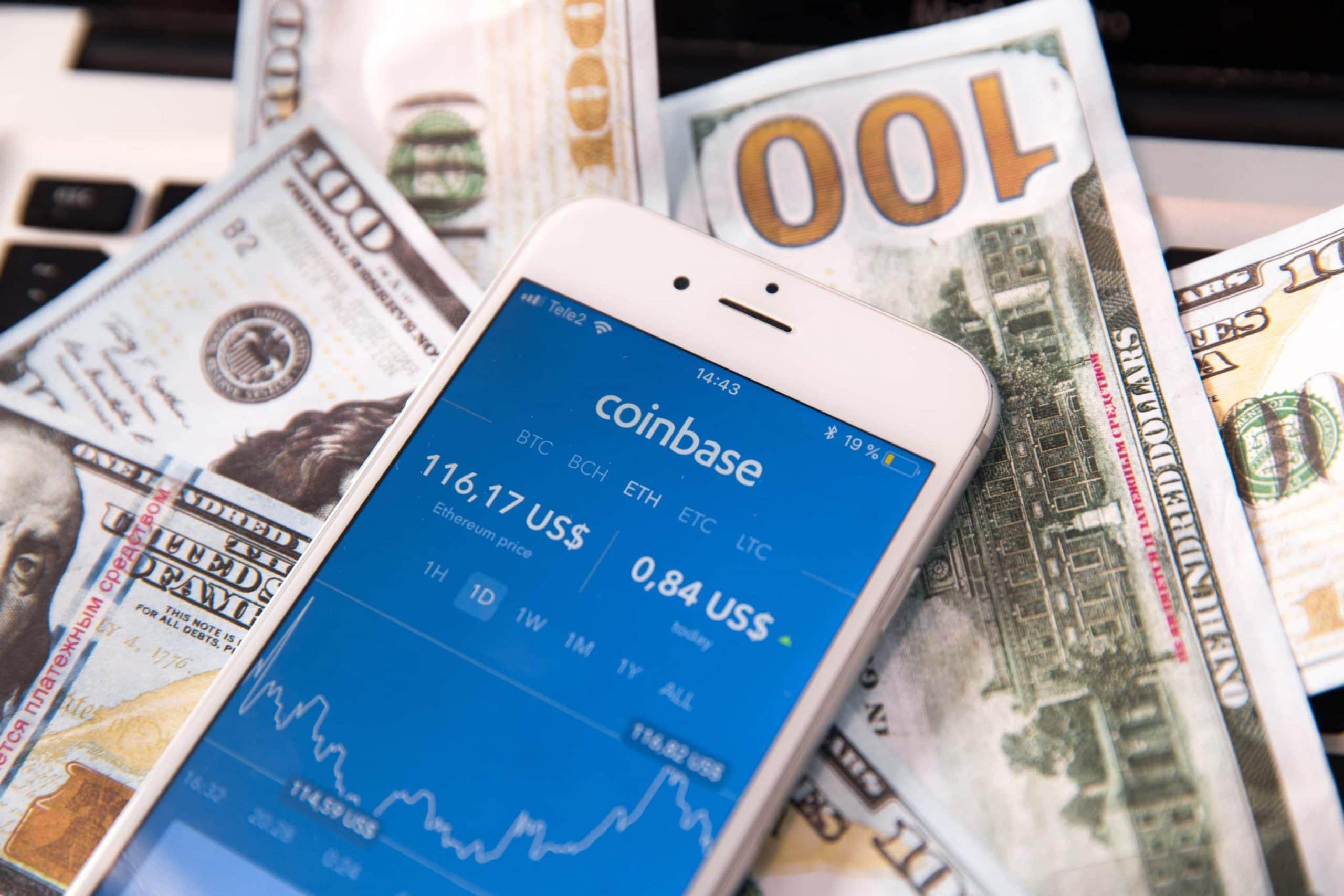 Ein Smartphone-Bildschirm mit geöffneter Coinbase-App liegt auf mehreren Geld-Noten