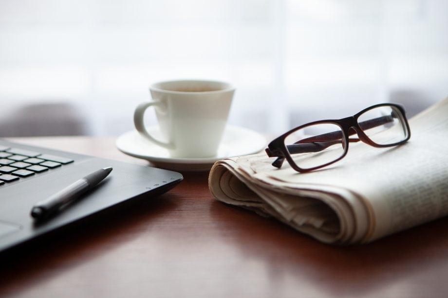 Ein Laptop, auf dem ein Kugelschreiber liegt, eine Kaffeetasse und eine Zeitung, auf der eine Brille liegt, liegen auf einem Holztisch.