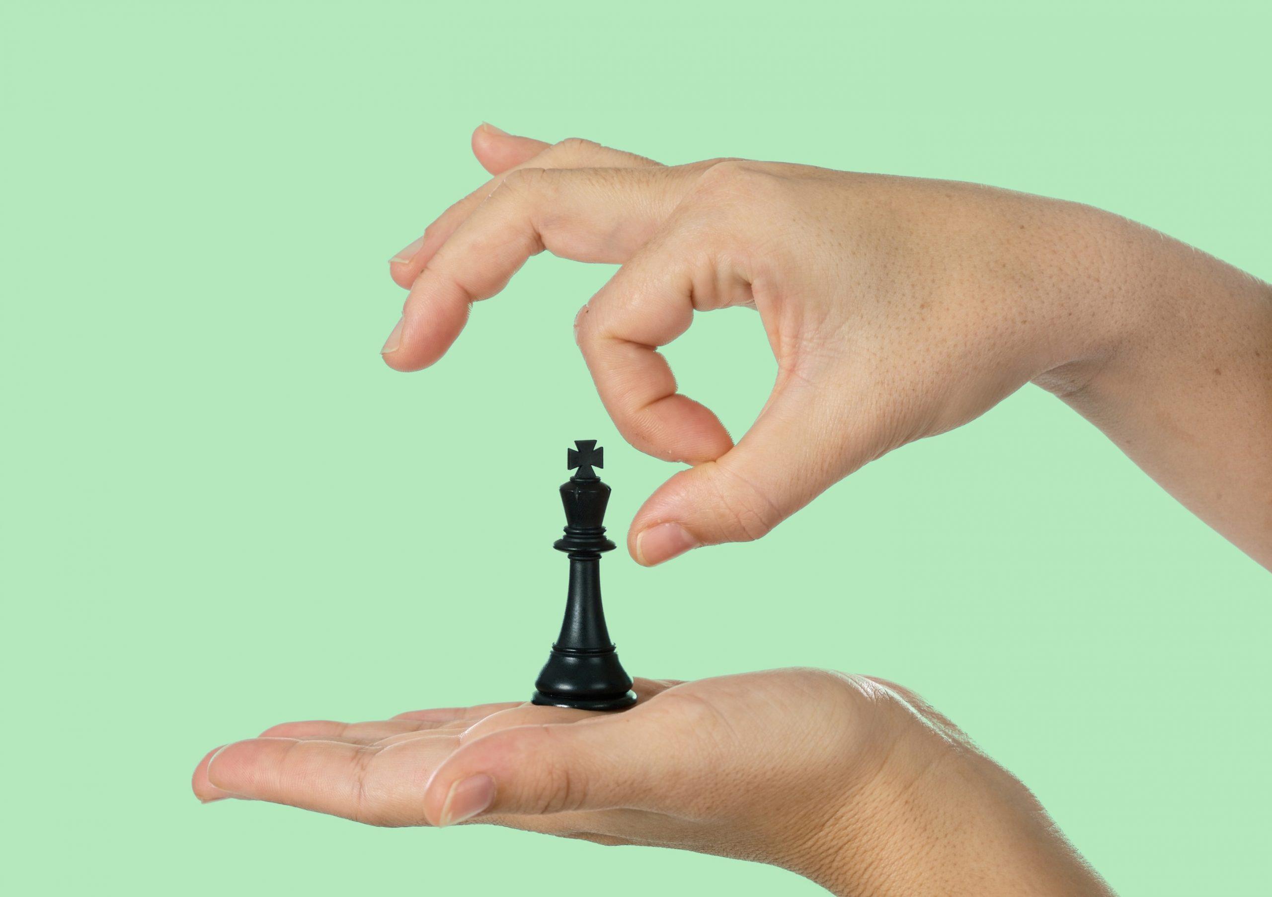 Eine Flache hand hält eine Schachfigur, die in Begriff ist, von einer anderen Hand weggeschnippst zu werden