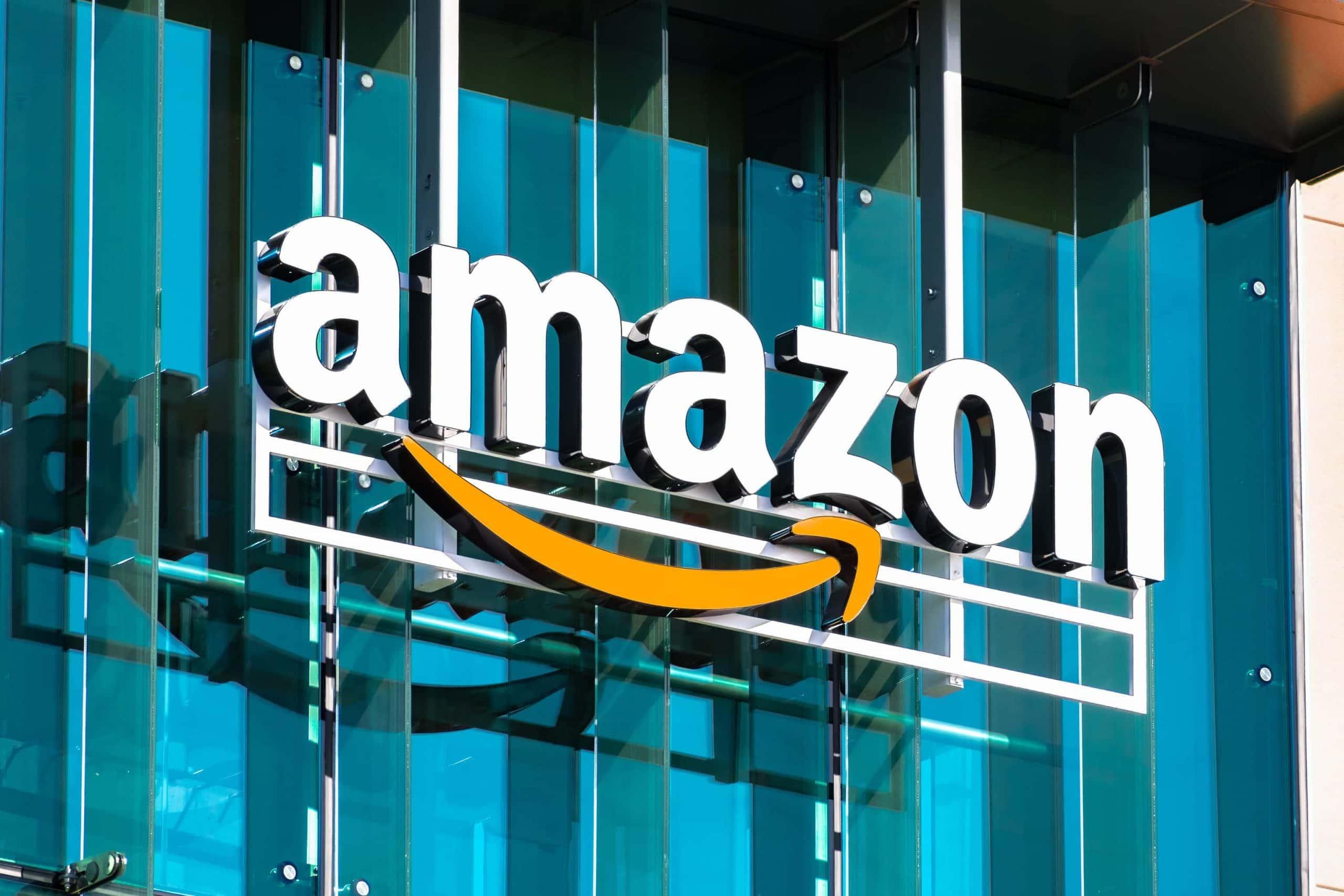 Amazon-Logo vor einer gläsernen Gebäudefassade.