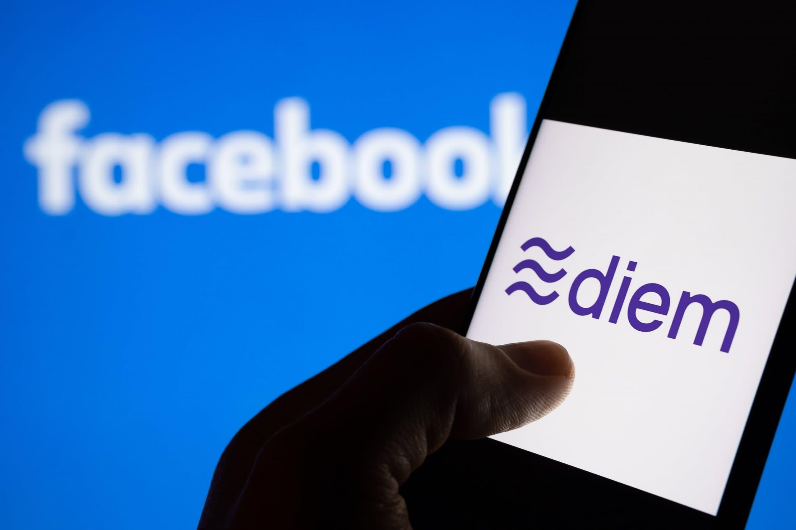 Eine Hand bedient ein Smartphone, auf dessen Bildschirm das Diem-Logo zu sehen ist. Im Hintergrund prangt das Facebook-Logo.