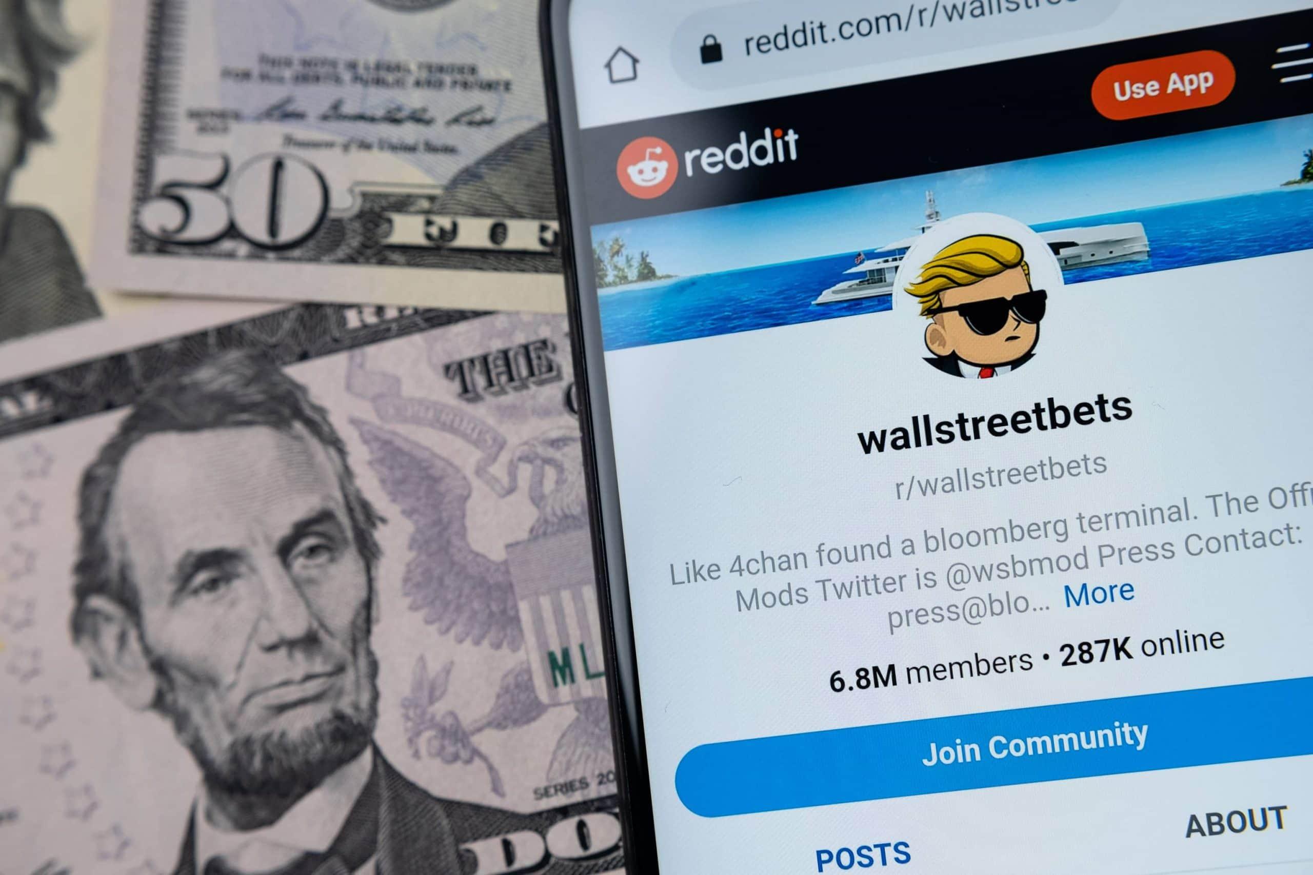 Ein Smartphone-Bildschirm liegt neben mehreren Dollar-Noten. Auf dem Bildschirm ist die Reddit-Seite der WallStreetBets zu sehen.