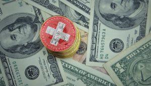 Bitcoin-Münze mit Schweizer Nationalfarben auf Dollar-Scheinen