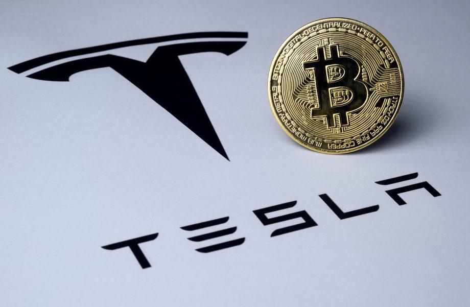 Ein Bitcoin neben dem Logo des US-Autobauers Tesla.