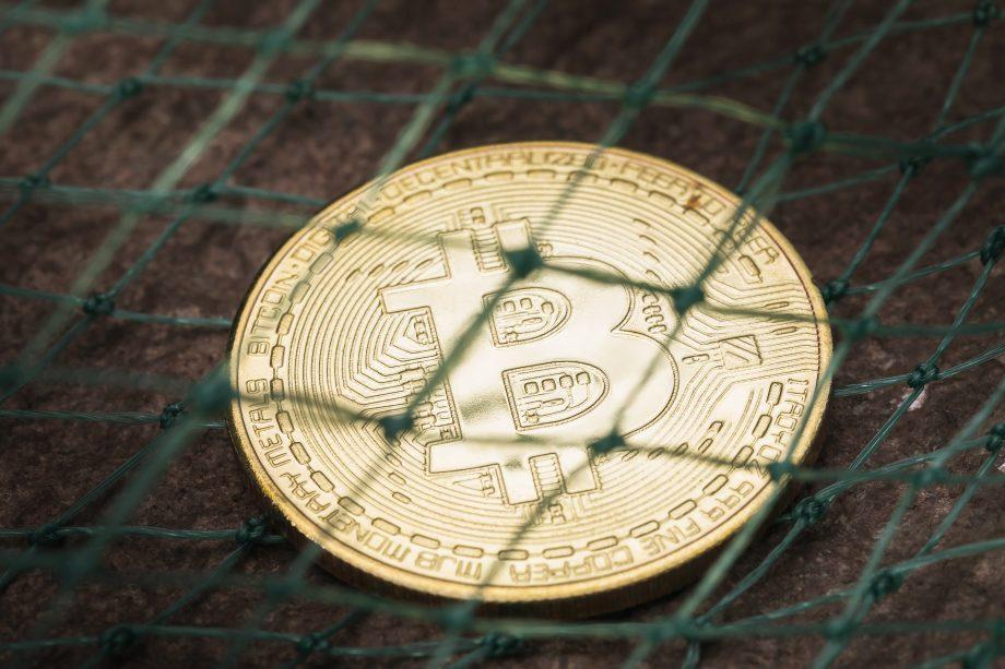 Bitcoin-Münze unter einem Netz