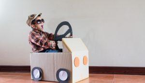 Kind sitzt im Rennwagen aus Pappe, der den Hype um Social Token symbolisieren soll.