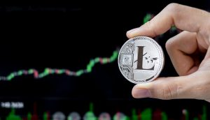 Litecoin-Münze wird vor einem Chart gehalten