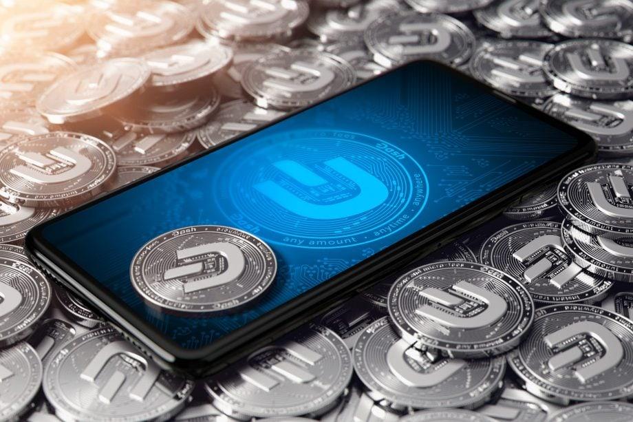 Smartphone Bildschirm mit Dash-Logo. Drumherum sind silberne Dash-Münzen.