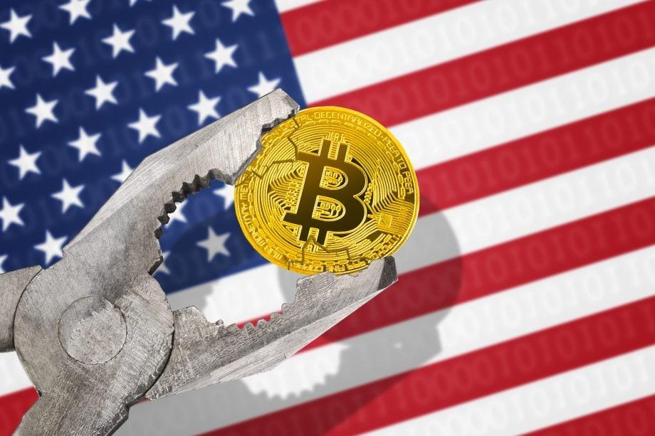 Bitcoin-Münze in einer Zange, im Hintergrund die USA-Flagge. Symbolbild Krypto-Regulierung in den USA