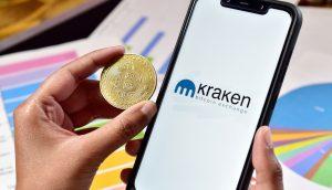 Bitcoin-Münuze neben Smartphone mit Kraken-Logo, im Hintergrund Balken- und Torten-Diagramme