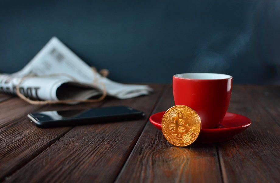 Eine Zeitung, ein schwarzes Smartphone, eine rote Kaffeetasse mit Untersetzer und eine Bitcoin-Münze stehen auf einem Holztisch.