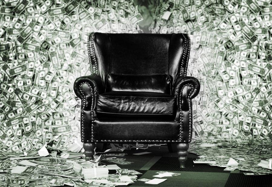 Ein schwarzer Sessel steht vor einem riesigen Haufen von US-Dollar-Noten