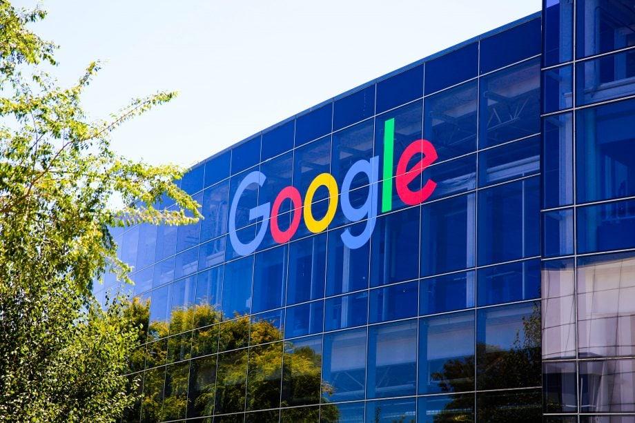 Das Firmenlogo von Google an einer gläsernen Gebäudefassade.