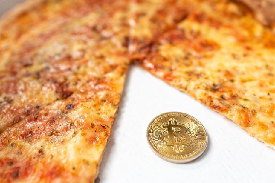 Bitcoin-Münze neben einer geschnittenen Pizza