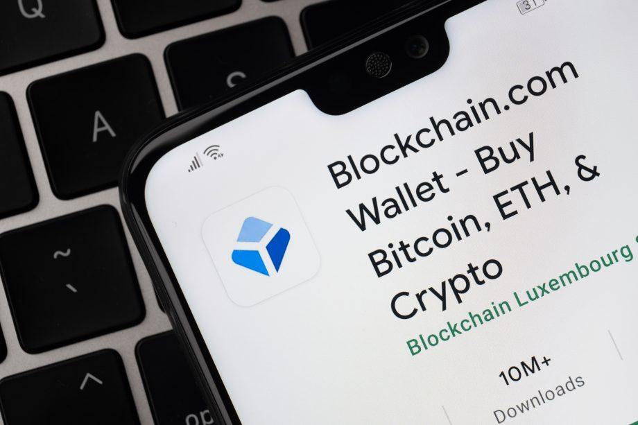 Auf einem Smartphone-Bildschirm ist die App von Blockchain.com geöffnet. Das Handy liegt auf einer Computertastatur.