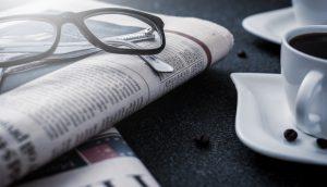 Eine Brille liegt auf einem Stapel Zeitungen. Daneben steht eine weiße Kaffeetasse mit Untersetzer.
