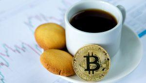 Kaffe-Tasse mit Gebäck und einem Bitcoin auf der Untertasse steht auf einer Unterlage, die aus Kurs-Diagrammen besteht.