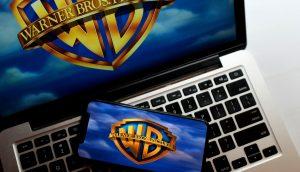 Warner-Logo auf Laptop und Smartphone