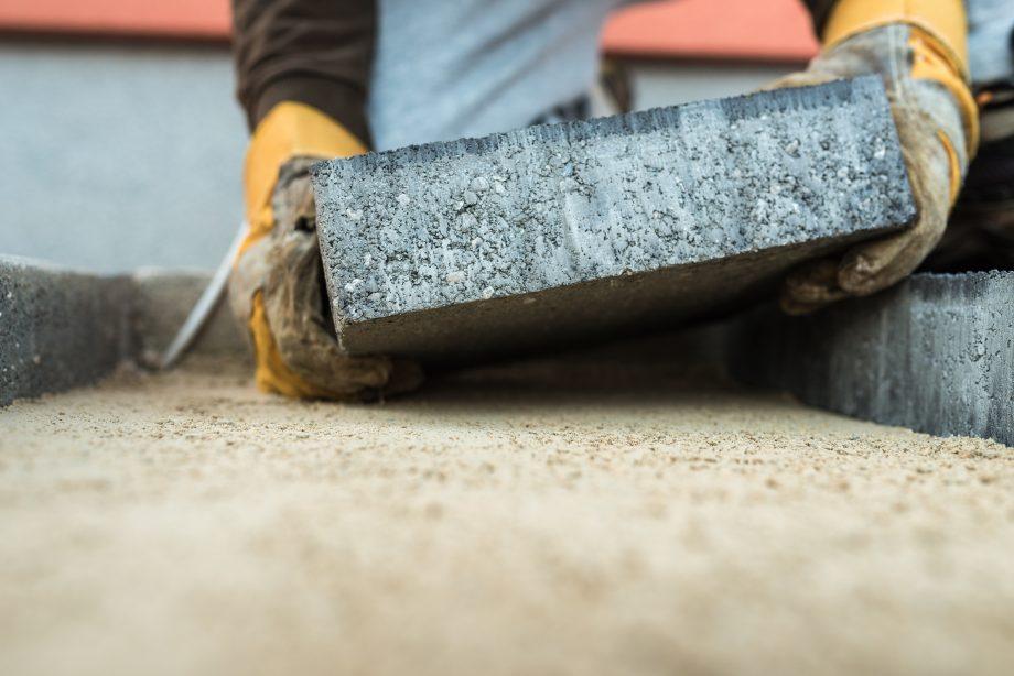 Bauarbeiter legt einen Stein auf den Boden