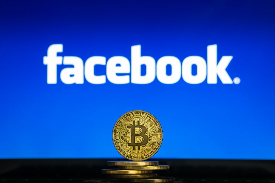 Bitcoin-Münze vor Facebook-Logo