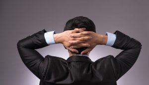 Geschäftsmann schlägt die Arme über den Kopf